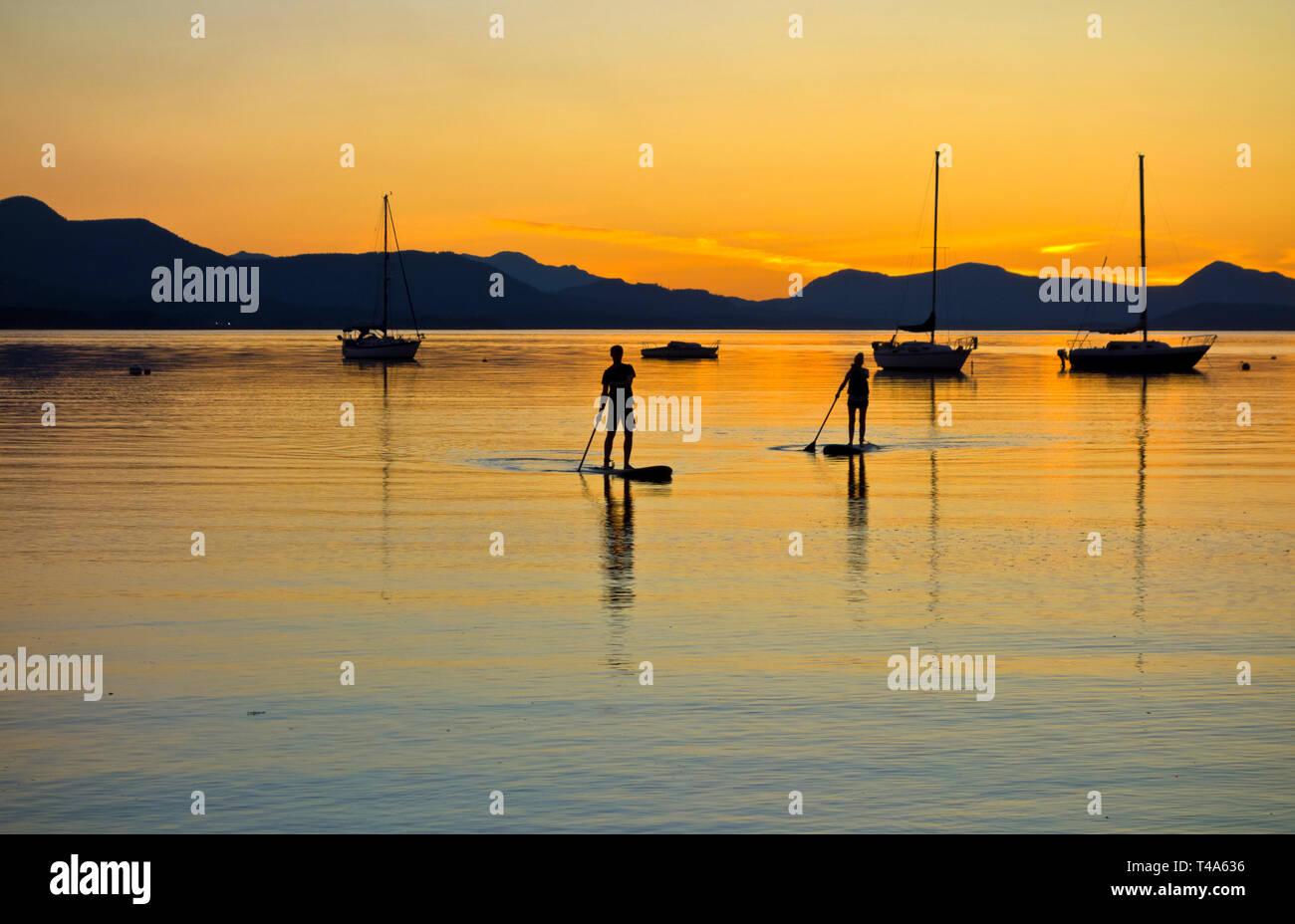 Deux stand up paddle boarders de revenir après le coucher du soleil à Salt Spring Island, en Colombie-Britannique, Canada. Stand up paddleboarding dans le sud des îles Gulf, en Colombie-Britannique. Banque D'Images