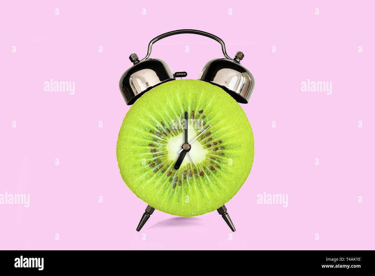 Tranche de kiwi sur le réveil, rose pastel arrière-plan. fruits et vitamines alimentation nutrition concept au petit déjeuner Photo Stock