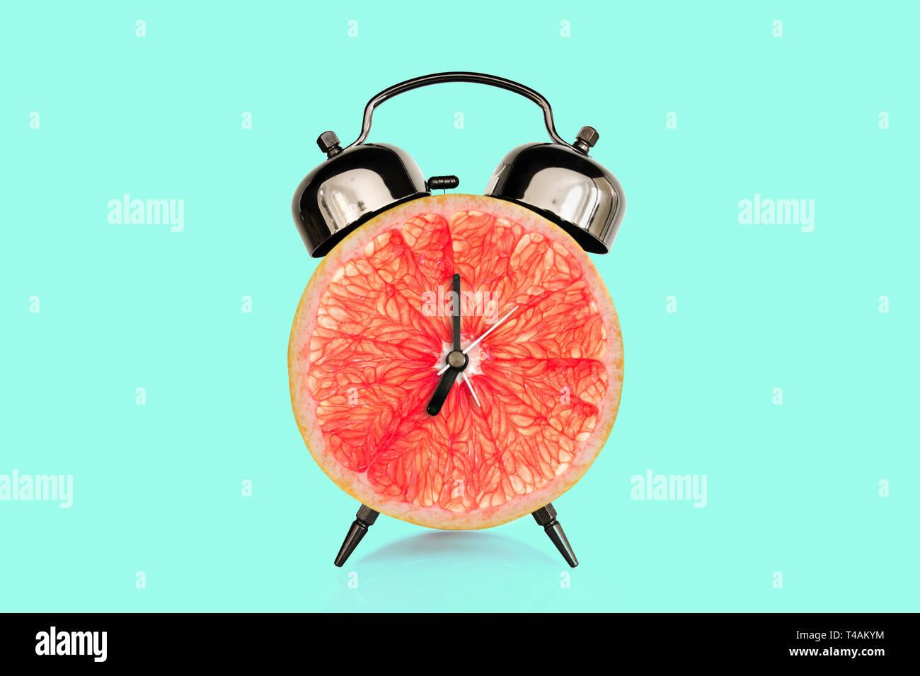 Tranche de pamplemousse, sur fond bleu pastel. fruits et vitamines alimentation nutrition concept au petit déjeuner Photo Stock