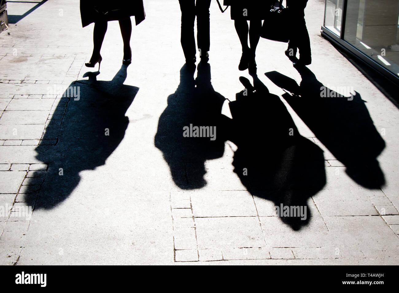 Ombre floue silhouette de personnes marchant sur la rue piétonne de la ville en noir et blanc à contraste élevé Banque D'Images
