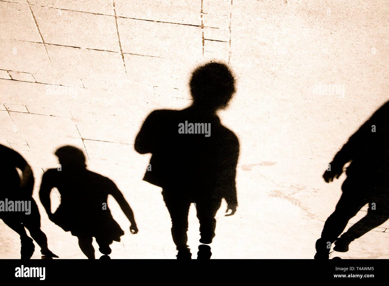 Blurrry ombre silhouete de personnes marchant sur la rue piétonne à contraste élevé sépia Noir et blanc Banque D'Images