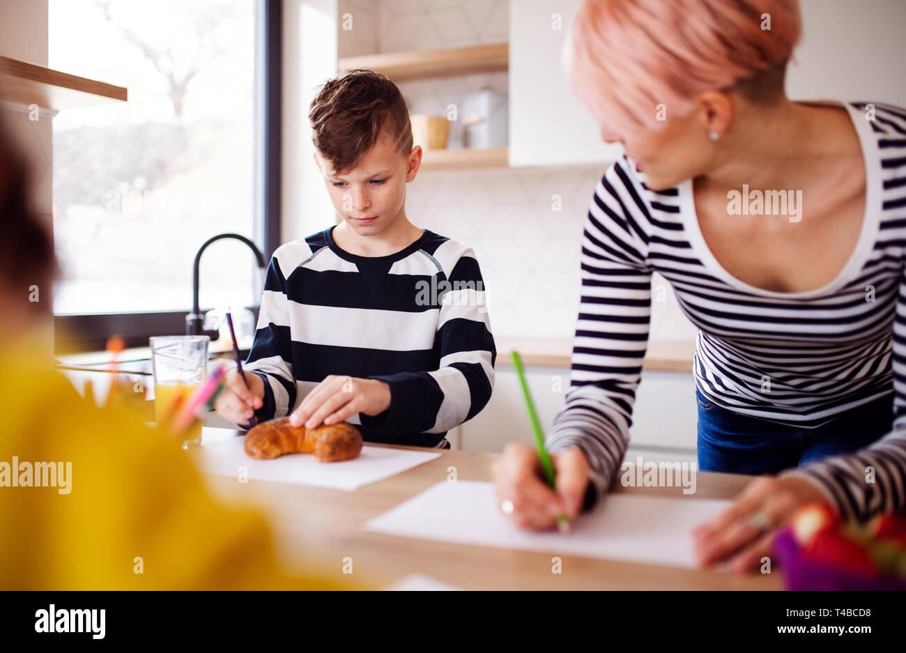 Une jeune femme avec deux enfants dessin dans une cuisine. Banque D'Images