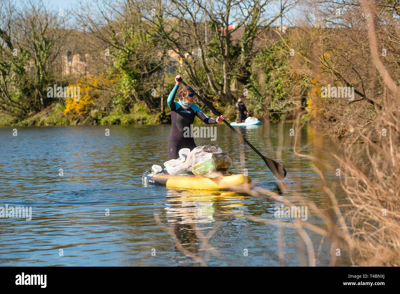 Deux femmes adultes on stand up paddleboards participant volontairement dans une rivière propre, décrochant le plastique et d'autres types des déchets, organisé par plage d'Aberystwyth Buddies / Gwerin y Glannau Rheidol le long de la rivière à Aberystwyth, Pays de Galles UK Banque D'Images