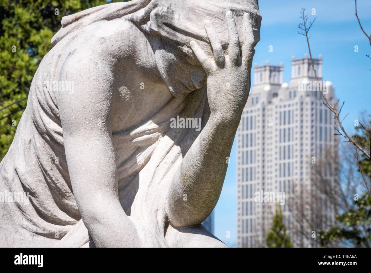 La statue de la femme en pleurs en lot gris Oakland Historique cimetière avec le centre-ville d'Atlanta, Georgia's 191 Peachtree Tower en arrière-plan. (USA) Photo Stock