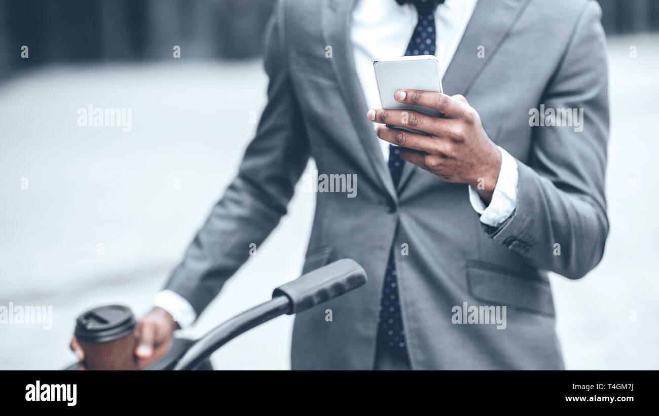 Businessman texting on phone, debout avec location Banque D'Images