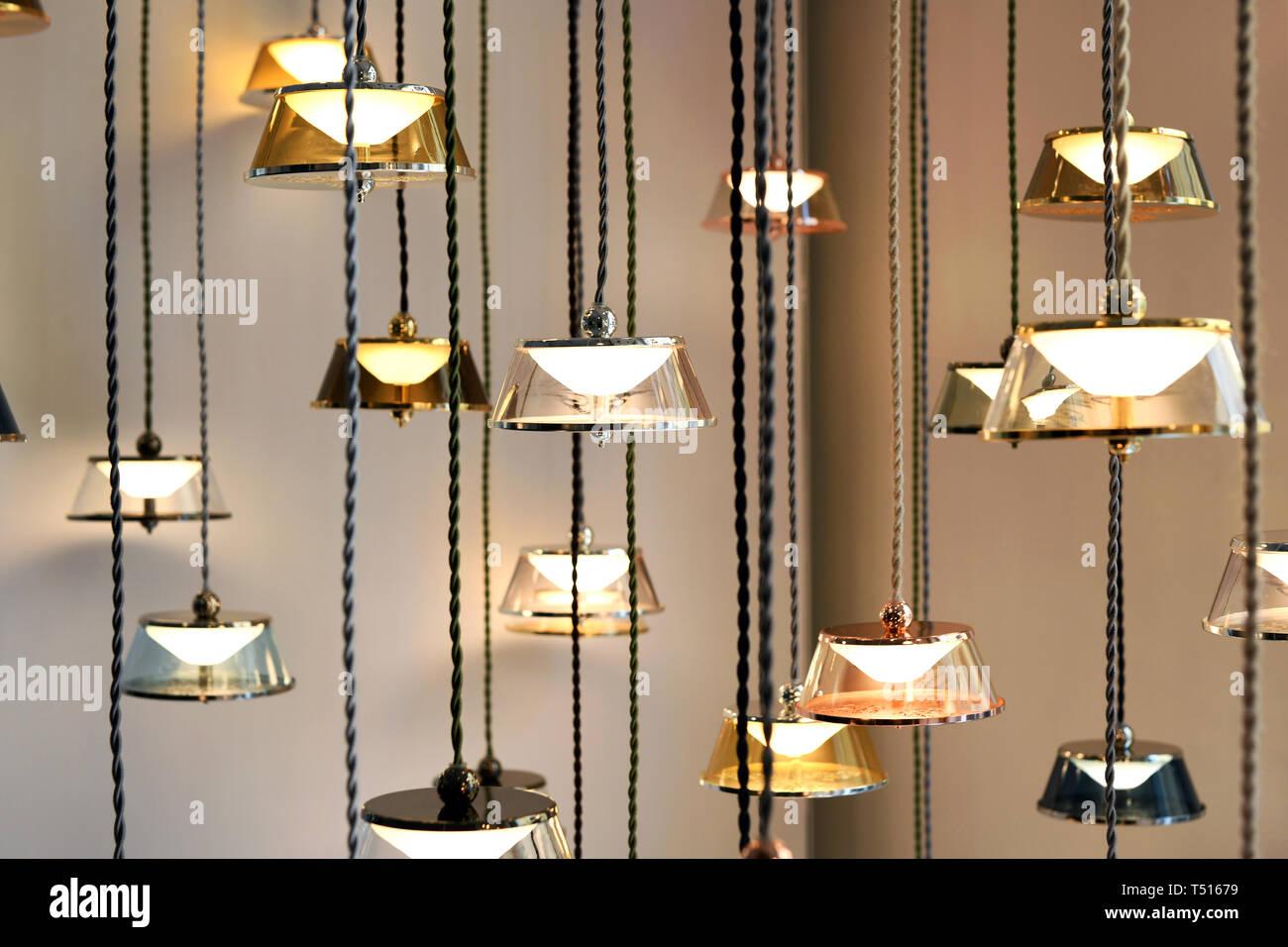 Design moderne avec lampes lustres lumineux avec une lumière chaude, suspendu à des fils contre mur gris Photo Stock