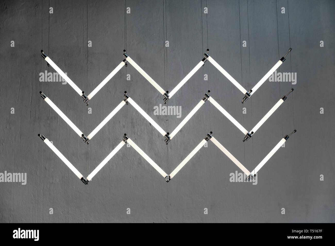 La conception moderne de l'éclairage au néon en zigzaguant solution avec lampes blanc brillant accroché sur les fils minces contre mur gris Photo Stock