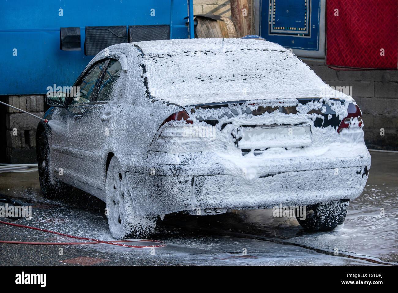 Lave-voiture noire avec mousse active. L'homme se lave machine à mousse. Location Dans l'état de lave-linge à la gare Banque D'Images