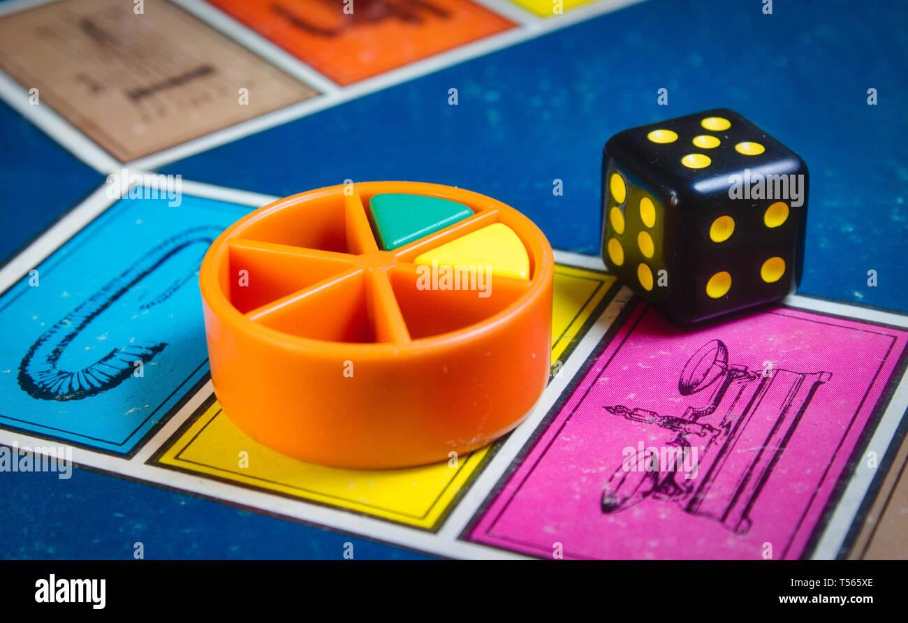 Londres, Royaume-Uni - 07 Avril 2019: classique jeu de Trivial Pursuit avec die noir et pièces en plastique de couleur de différentes couleurs Banque D'Images