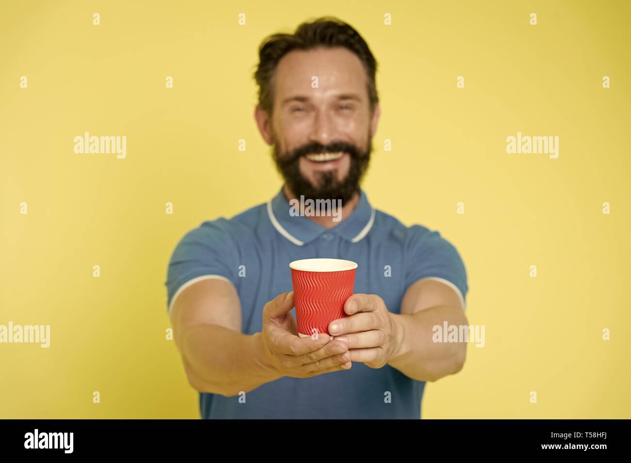 Guy barbe et moustache contient le papier une tasse de thé ou café. Offrir un verre pour vous. Soins Homme expérimenté formateur sur le bilan hydrique. Partager et générosité concept. Avoir une gorgée. Prenez-le si vous voulez boire. Photo Stock