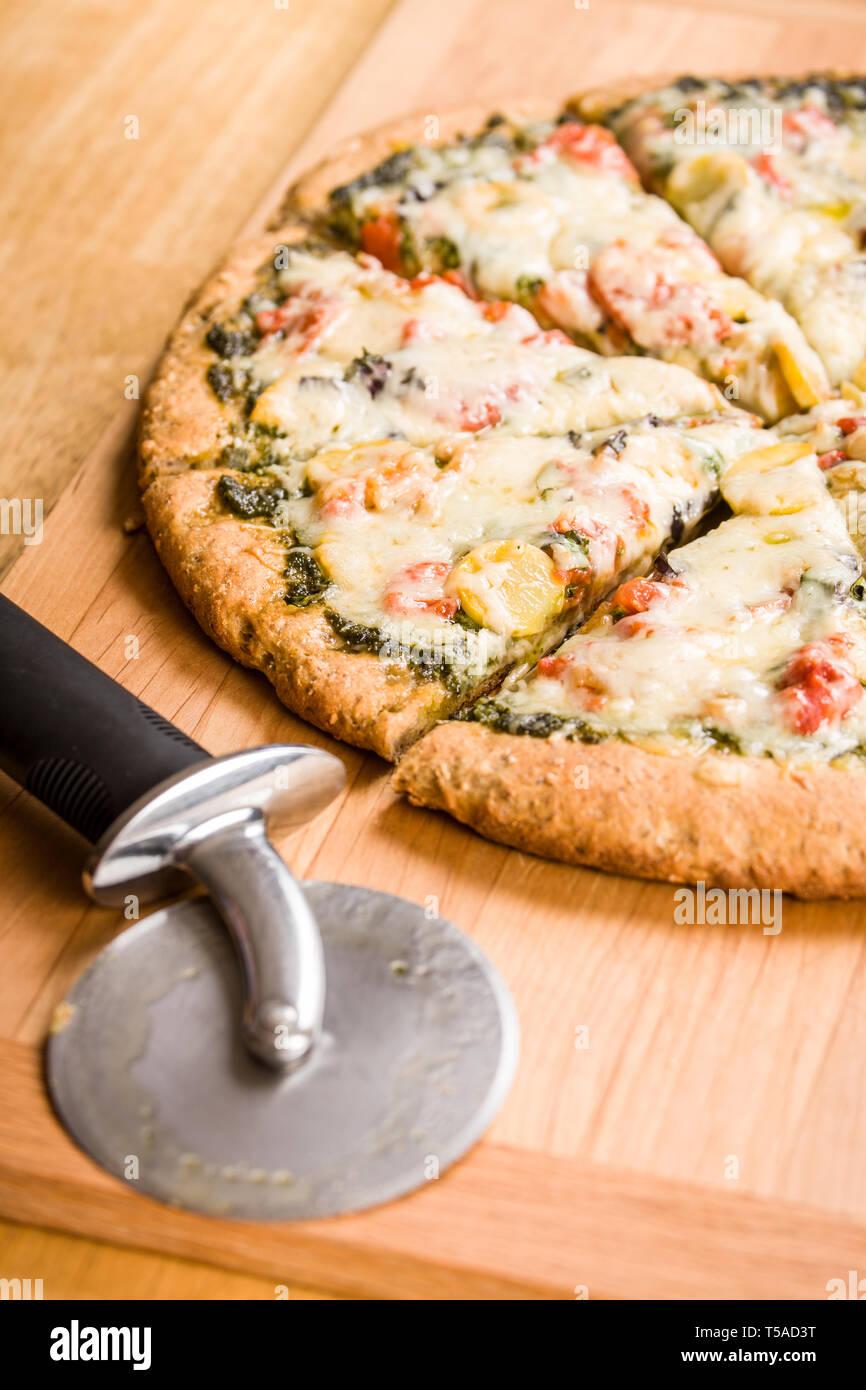 Coupe pizza cuites au four et un, végétarien, pesto, multi-grains, des pizzas à pâte épaisse Banque D'Images