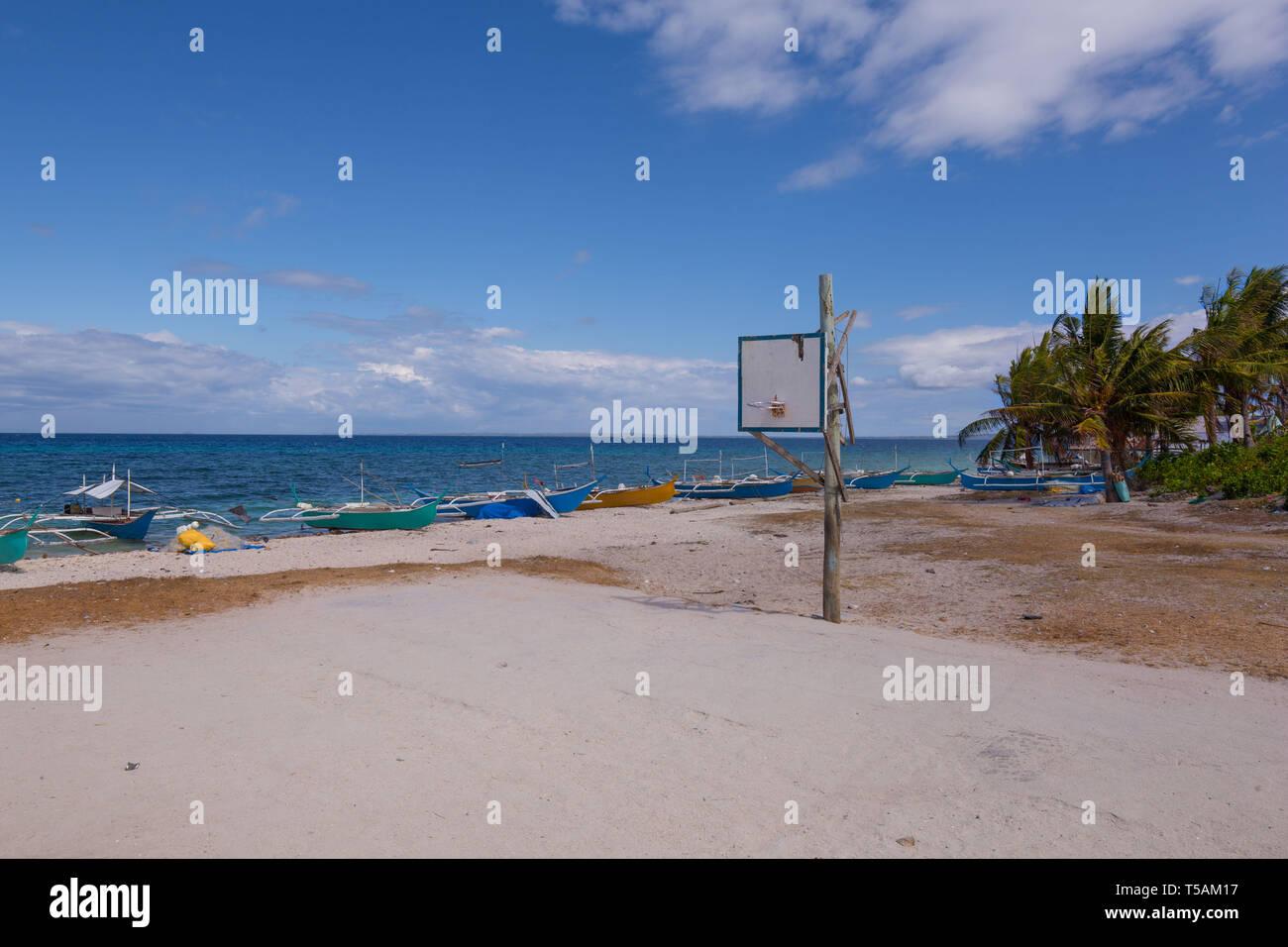 Un ciment simple terrain de basket-ball à la plage de sable blanc avec des bateaux, une simple scène de la vie rurale Photo Stock