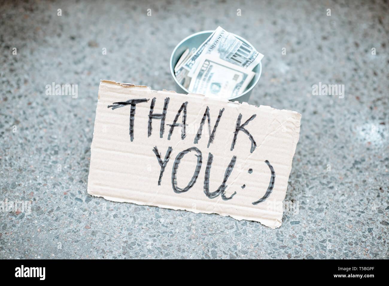 Beggar's cup avec de l'argent et le carton avec message de remerciement sur rue Photo Stock