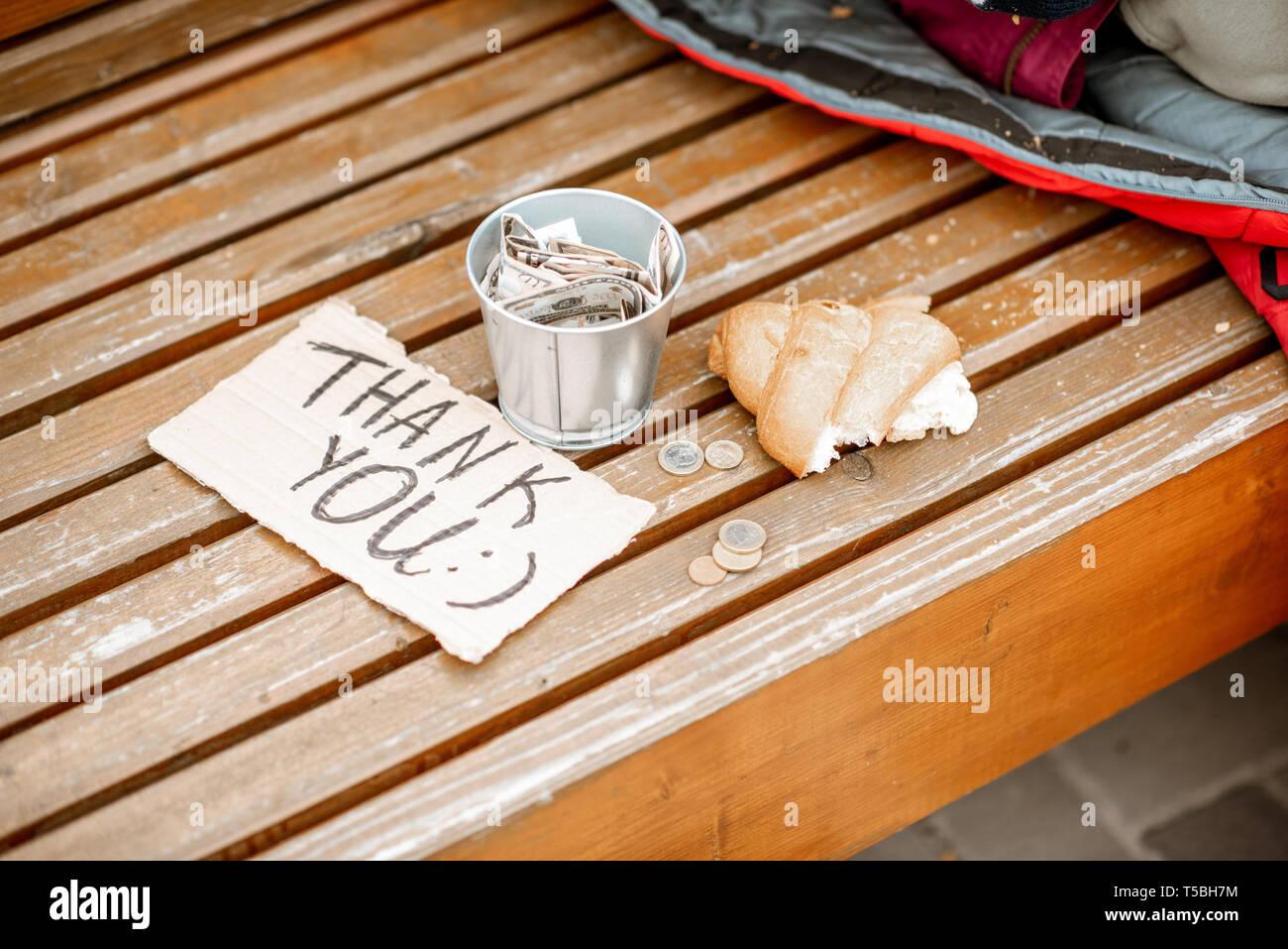 Beggar's cup avec message de remerciement et de pain sur le banc à l'extérieur. La mendicité money concept Photo Stock