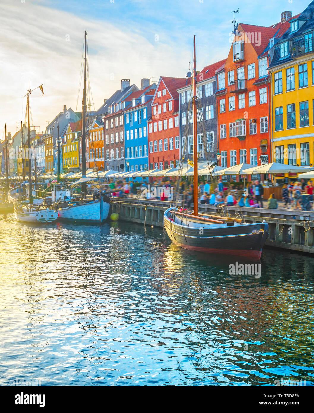 Voir Nyhavn avec des bateaux par remblai au coucher du soleil, les gens marcher et s'asseoir dans les restaurants, Copenhague, Danemark Banque D'Images