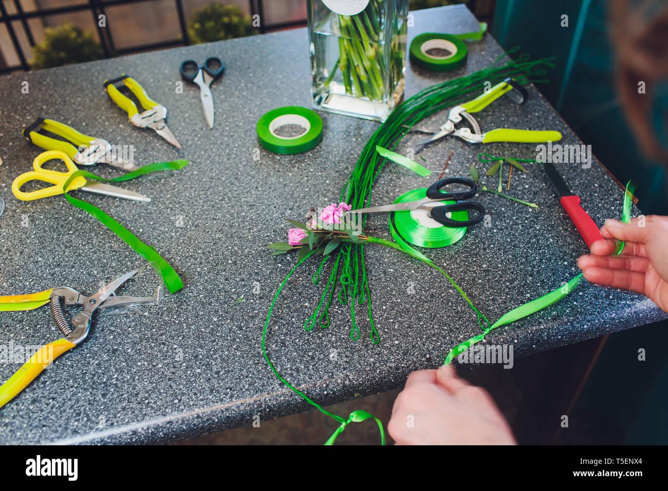 Processus de création d'un magasin de fleurs fleuriste bouquet close-up. Femme mains et à mettre en œuvre. Photo Stock