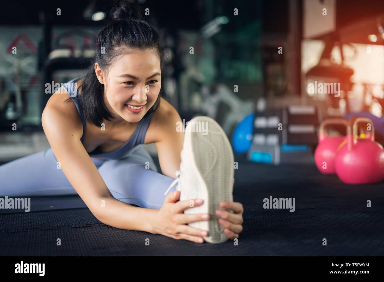 Young Asian Woman in healthy lifestyle assis sur un tapis de yoga étirement pied holding jambe. l'exercice et de remise en forme santé concept dans une salle de sport. Banque D'Images