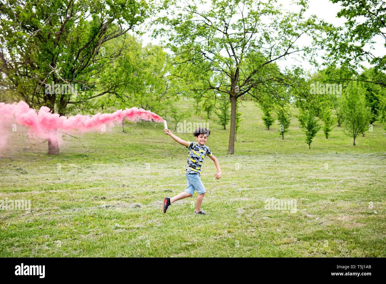 Jeune garçon courir avec un flare rose coloré de fuite de fumée rose derrière lui dans l'herbe dans un parc aux arbres de ressort Banque D'Images