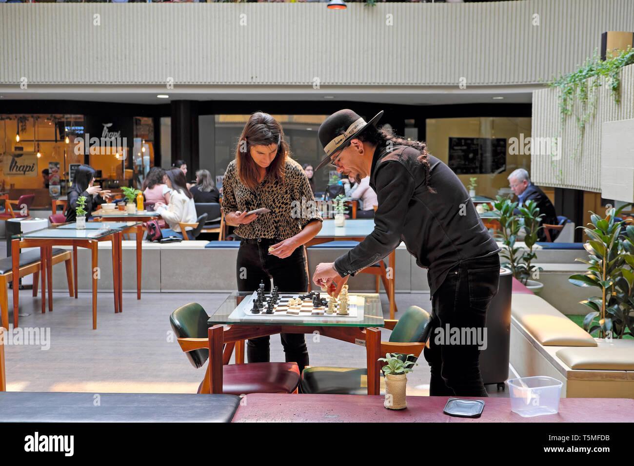 L'homme et la femme dans un café au Galerias Lumière mise en place d'un jeu d'échecs sur une table à l'intérieur du restaurant à Porto, Portugal Europe UE KATHY DEWITT Banque D'Images
