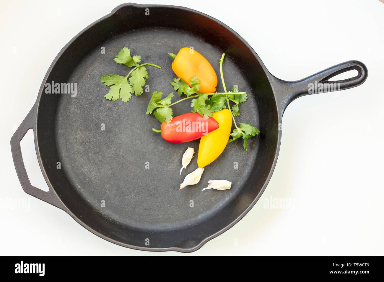 Blasck poêle en fonte avec rouge, jaune et orange, les poivrons, le persil et l'ail Photo Stock