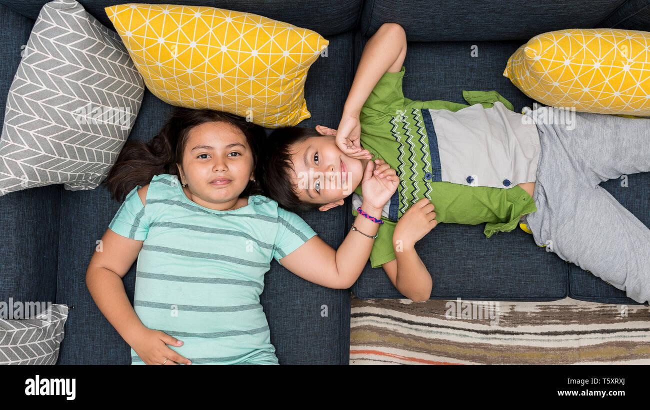 Technique mixte/caucasien asiatique frère et sœur portant sur canapé ensemble souriant à la caméra directement à. Banque D'Images