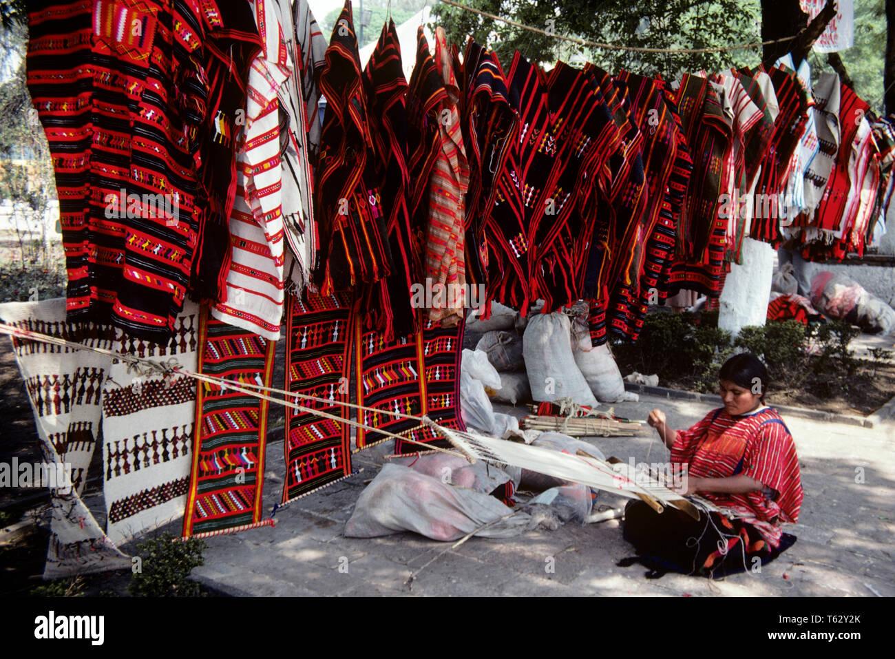 1980 WEAVER MEXICAIN MEXICO MEXIQUE SUR LE MARCHÉ À XOCHIMILCO - KR39963 KRU001 HARS MID-ADULT MID-ADULT WOMAN ATTRACTION TOURISTIQUE PRÈS D'ARTS ET MÉTIERS ARTISANAUX DE TISSAGE LOOM OLD FASHIONED WEAVER XOCHIMILCO Photo Stock