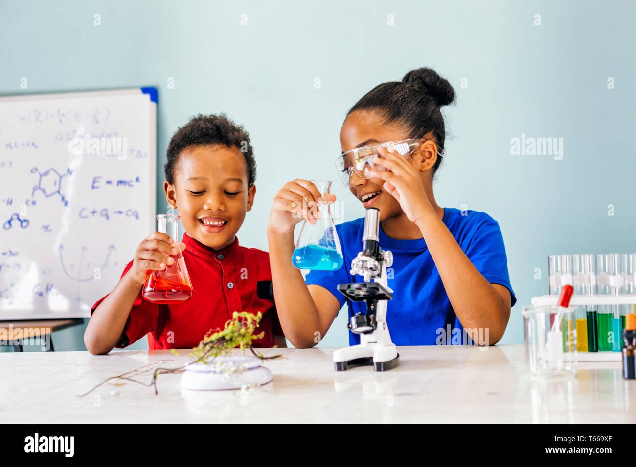 Deux enfants mixtes Afro-Américains et les tests de laboratoire de chimie holding tube verre ballon avec microscope et sourire en classe de sciences - concept Banque D'Images