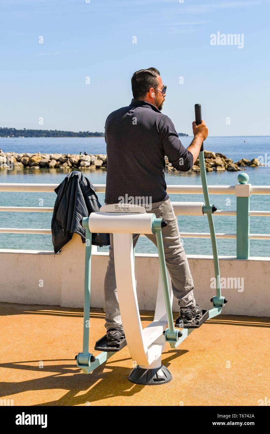 CANNES, FRANCE - Avril 2019: Personne à utiliser une machine de formation à un sport en plein air sur la promenade à Cannes Photo Stock