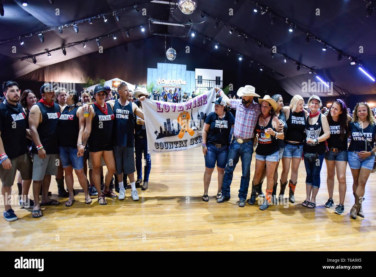 Indio, California - Avril 27, 2019 Rt 91 survivants avec un panneau, l'amour gagne à Stagecoach Country Music Festival. Banque D'Images