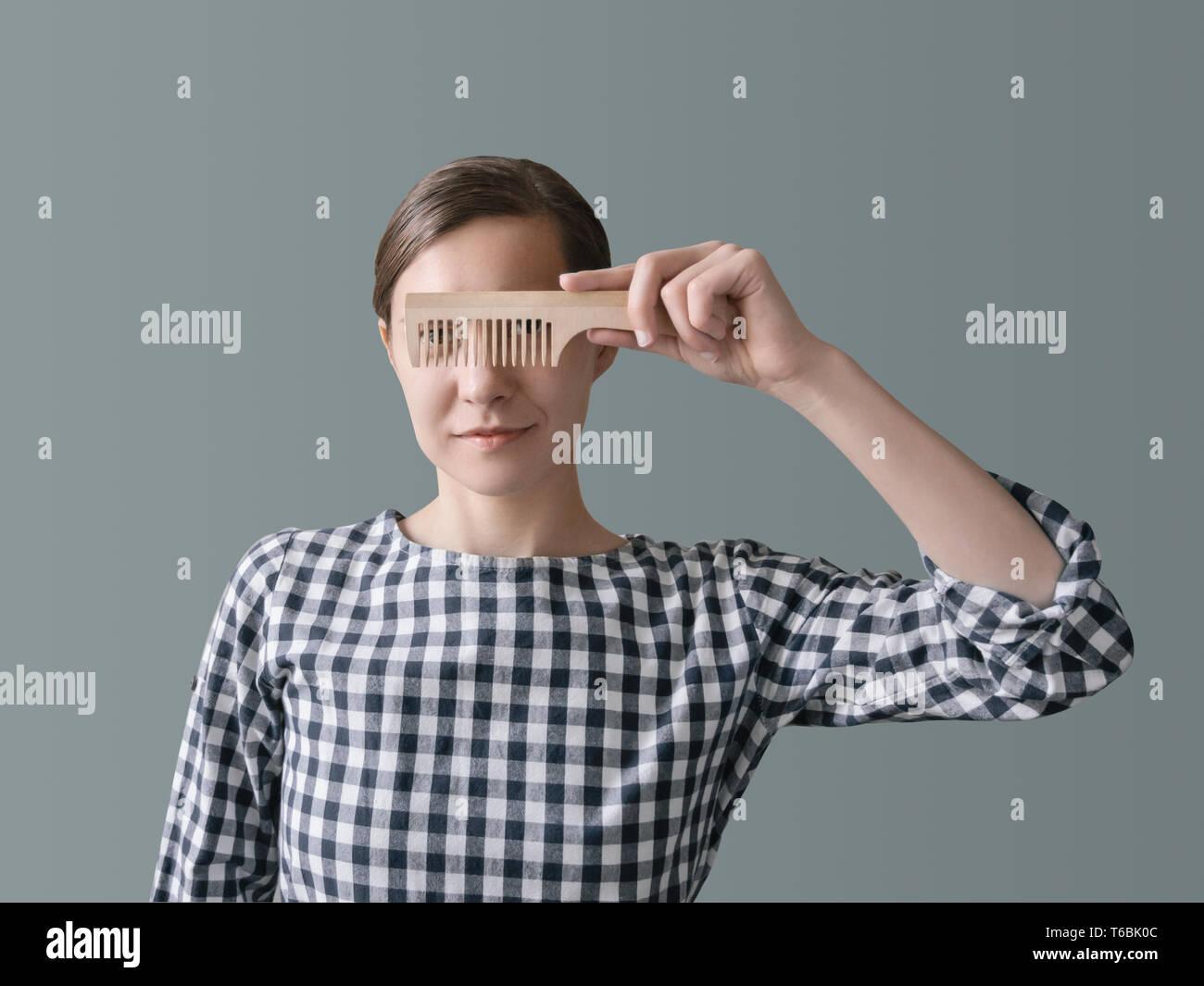 Eco concept zéro déchet produit la jeune fille à la robe à carreaux est titulaire d'un peigne en bois en face de son visage Banque D'Images