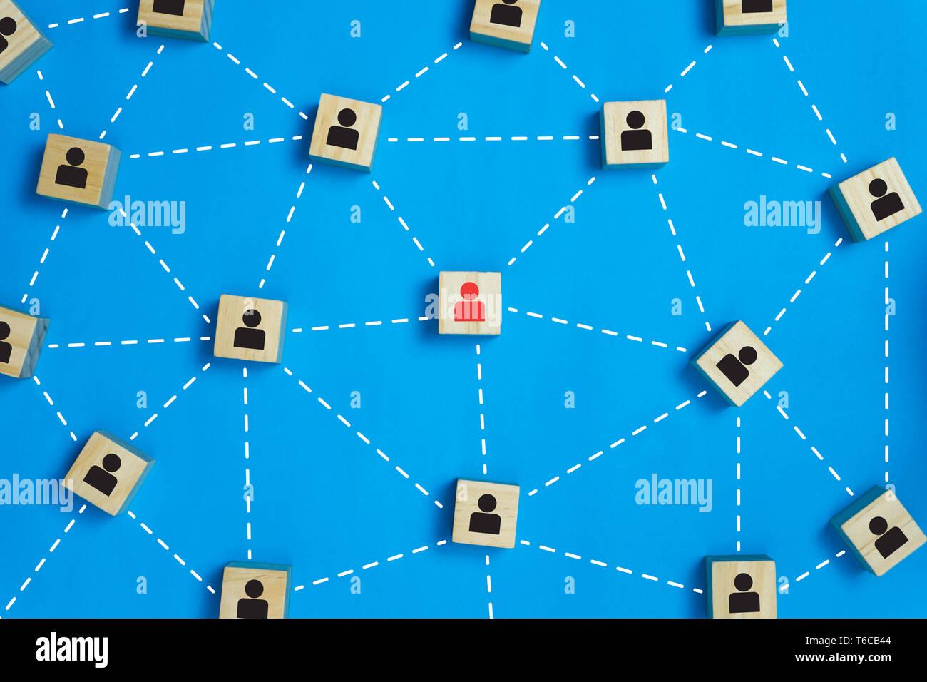 Le leadership et l'équipe du réseau d'affaires sur l'icône rouge concepts le bloc de bois au milieu entre la black business icône sur les blocs de bois. Banque D'Images