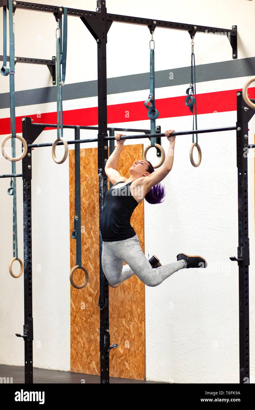 Jeune femme fit faire de l'athlète tirer-se lève sur sonne pendant que l'exercice dans une salle de sport au cours de sa séance d'entraînement pour renforcer ses muscles du haut du corps Photo Stock