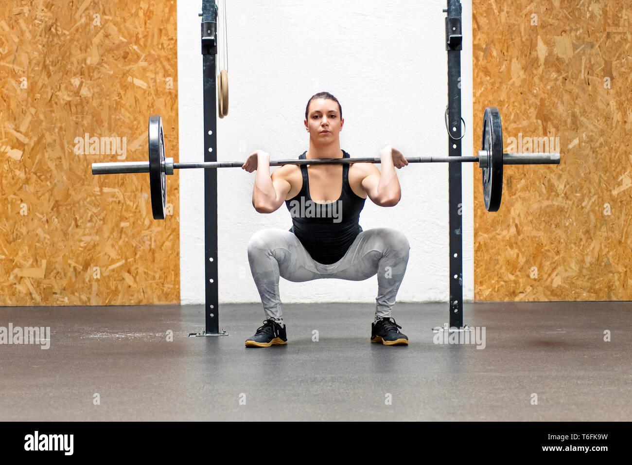 La jeune femme faisant un squat avant dans une salle de sport soulever un poids d'haltères à ses épaules pour renforcer ses quadriceps et fessiers Photo Stock