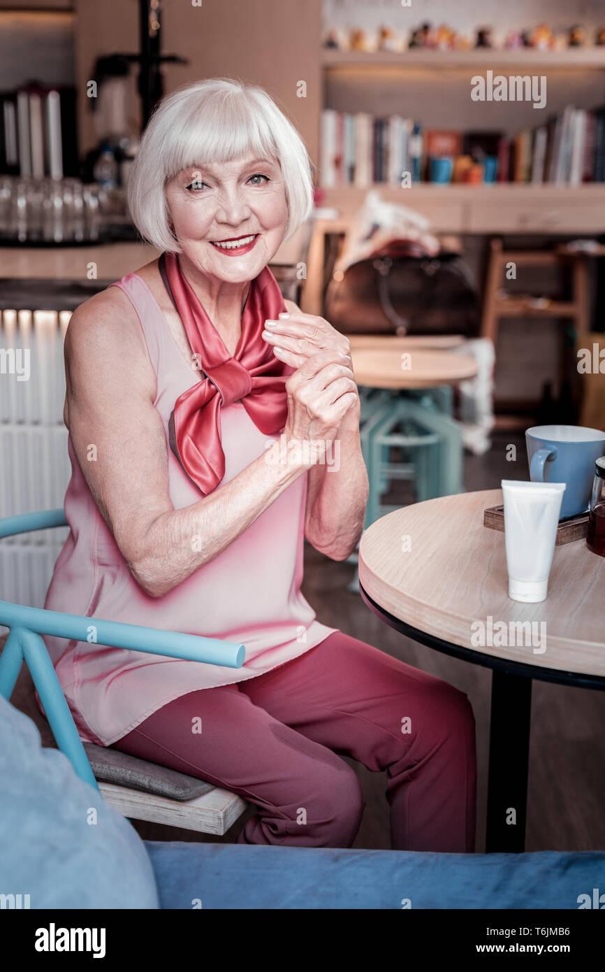 Joli short-haired vieille dame lui frottait les mains avec la crème de lissage Banque D'Images