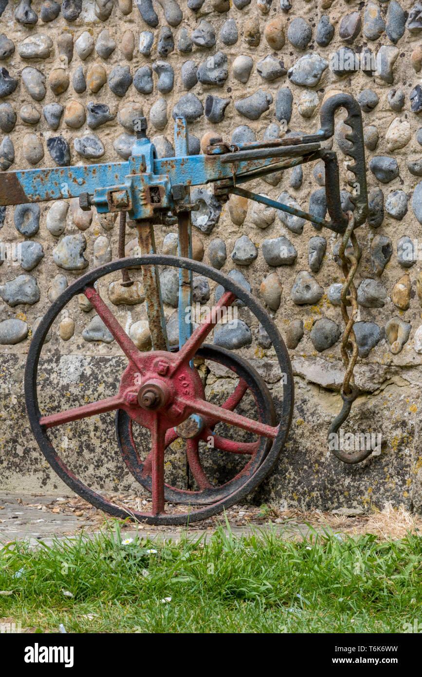Une ancienne charrue agricole tiré par des chevaux ou mettre en œuvre appuyée contre un mur de mortier et de silex de Sussex. Photo Stock