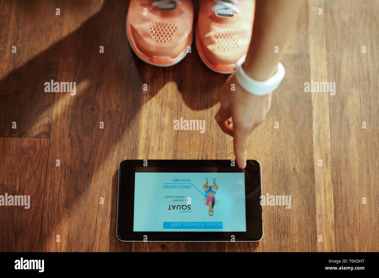 Gros plan sur une femme en vêtements de sport fitness dans le salon moderne à l'aide d'entraînement home trainer app en PC tablette. Banque D'Images