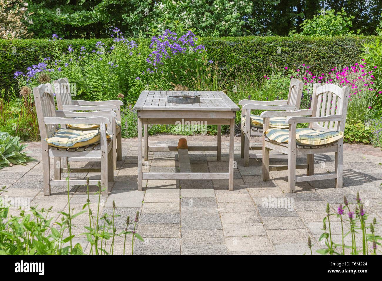 Table et chaises en bois dans un jardin ornemental Banque D'Images