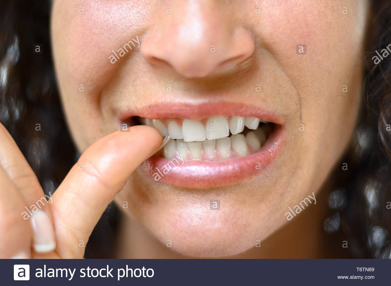 Anxieux young woman biting son pouce Photo Stock