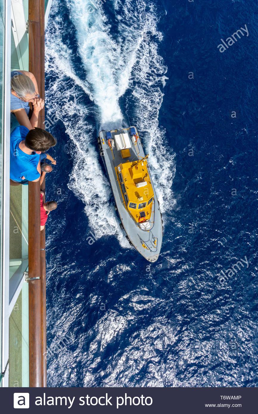 Les passagers des navires de croisière regarder un bateau pilote d'un projet pilote de retour à la Barbade, une île royaume de Commonwealth dans l'Atlantique Nord dans la région des Caraïbes. Banque D'Images