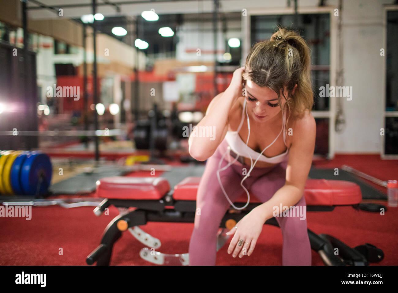 Blonde fit se reposant après une intense séance de formation à la salle de sport Banque D'Images