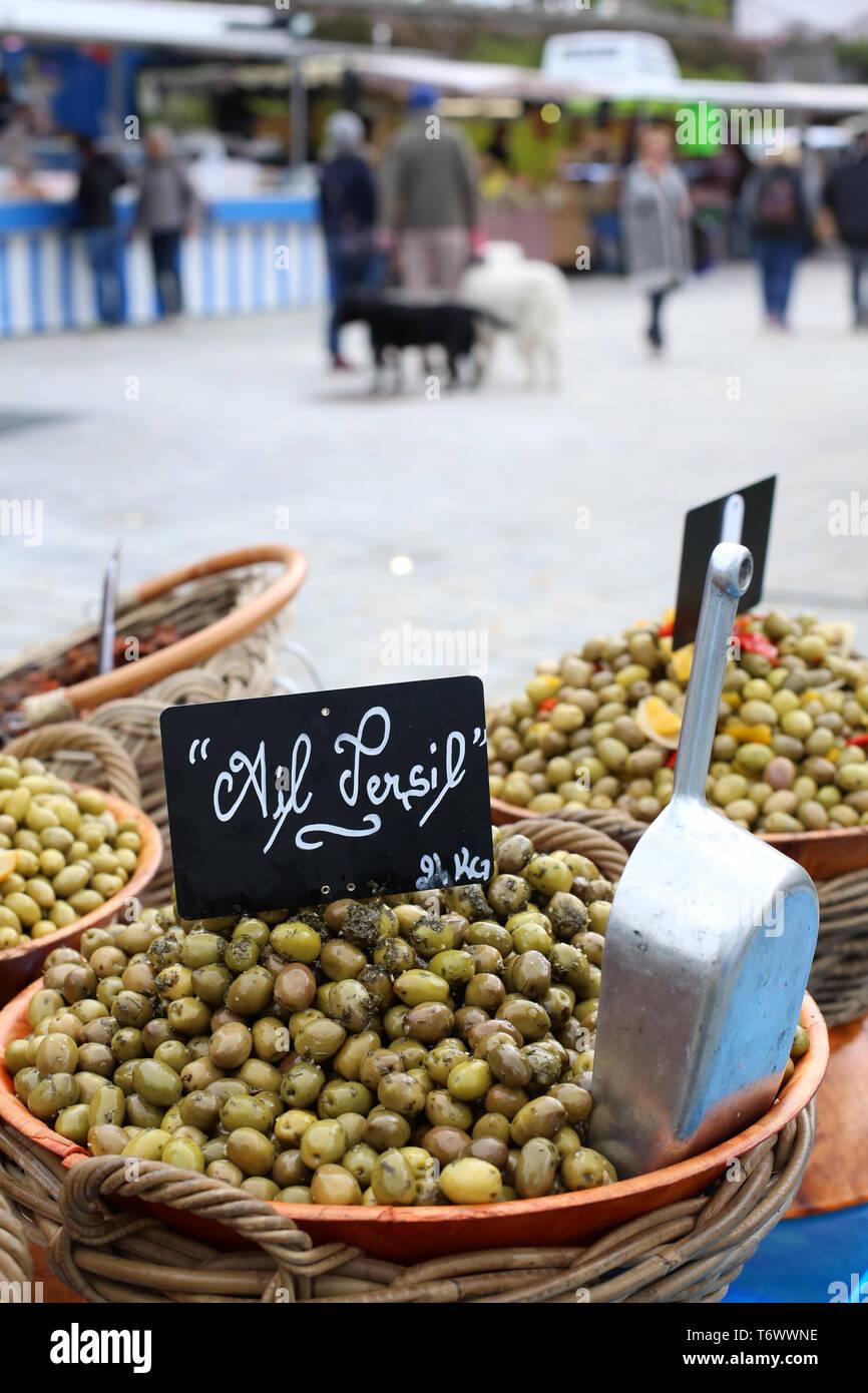 Vente d'olives vertes, ail et persil, sur un marché local. Banque D'Images