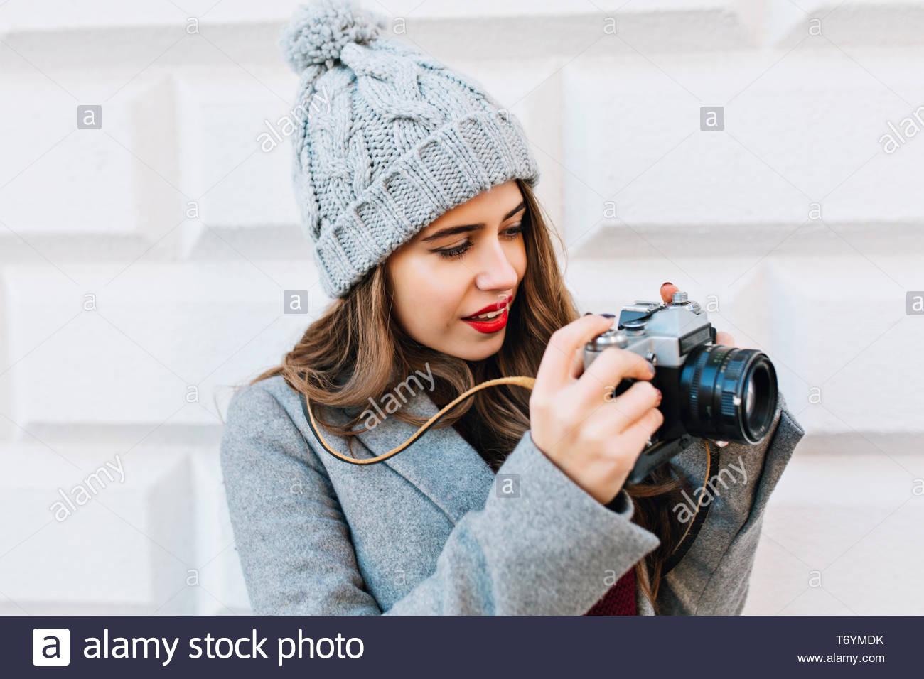 Closeup portrait jeune fille avec de longs cheveux en manteau gris sur fond de mur gris à l'extérieur. Elle est considérée comme l'appareil photo dans les mains Banque D'Images