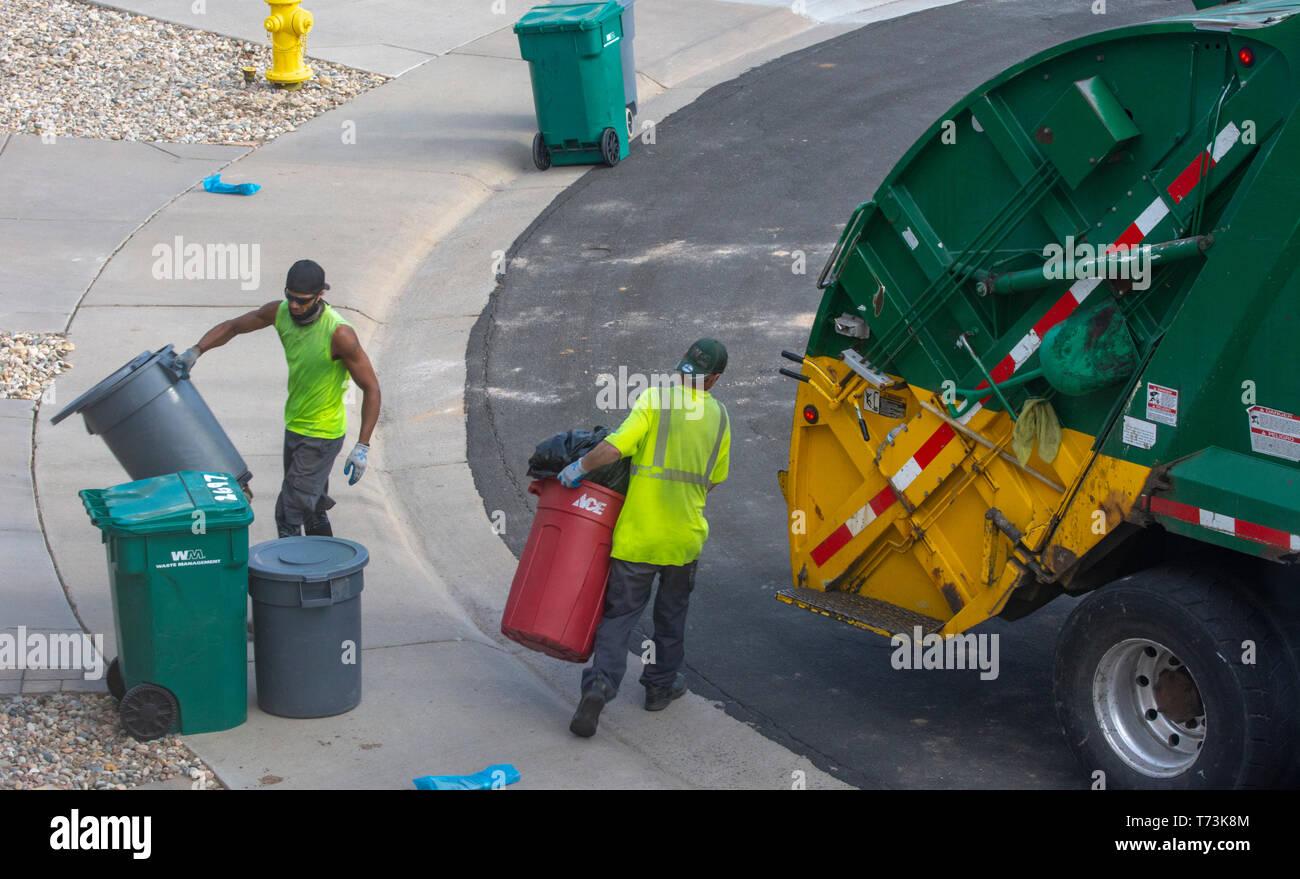 Deux travailleurs de la gestion des déchets en plastique gris et vert vide les poubelles dans une zone résidentielle, Castle Rock Colorado nous. Photo prise en avril. Photo Stock