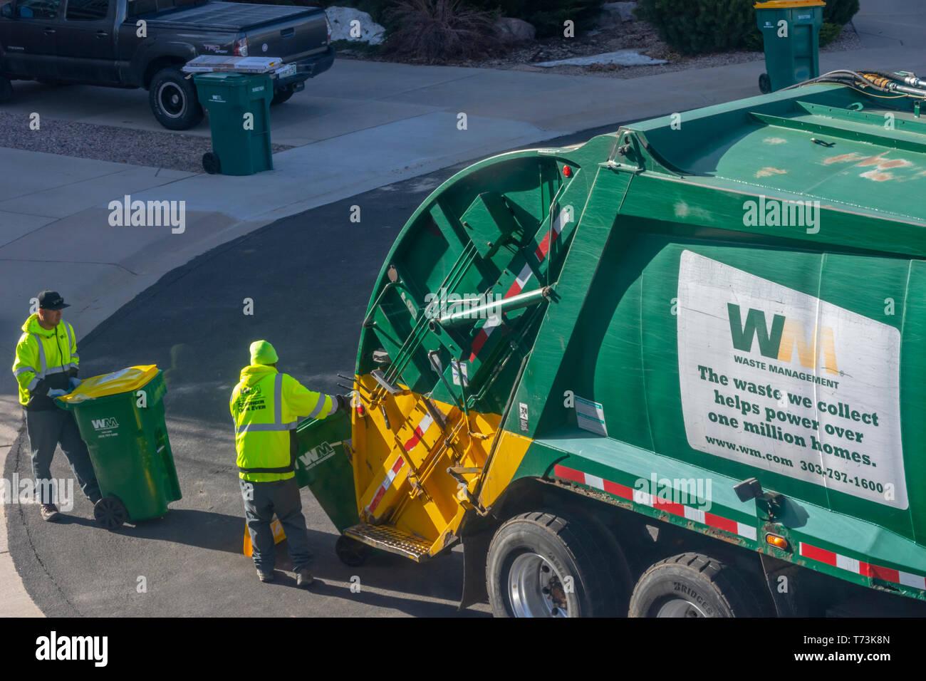 Deux travailleurs de la gestion des déchets en plastique jaune et vert vide les poubelles dans une zone résidentielle, Castle Rock Colorado nous. Photo prise en avril. Photo Stock