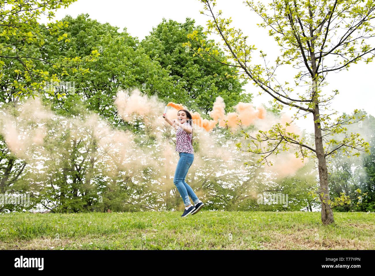 Heureuse jeune fille énergique avec une torche de fumée courir et sauter dans un jardin rire avec excitation Banque D'Images