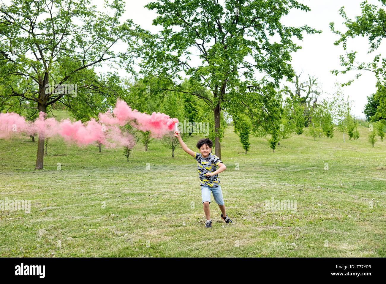 Jeune garçon qui traverse un parc au début du printemps une fuite de fumée rose flare derrière lui Banque D'Images