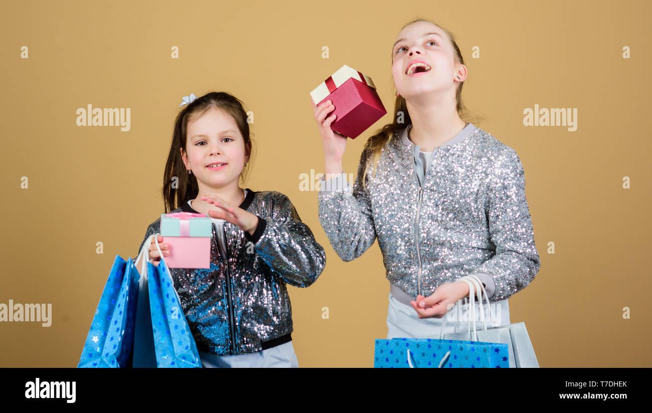 Sisterhood. Achats de vacances. Ventes et Promotions. Kid fashion. shop assistant avec emballage. Les petites filles avec des sacs d'emplettes. Des enfants heureux. Petite fille soeurs avec boîte-cadeau. Shopping ensemble. Photo Stock