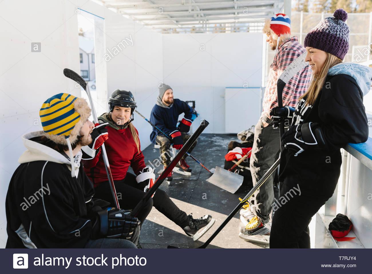Les amis de prendre une pause de jouer au hockey sur glace en plein air Photo Stock