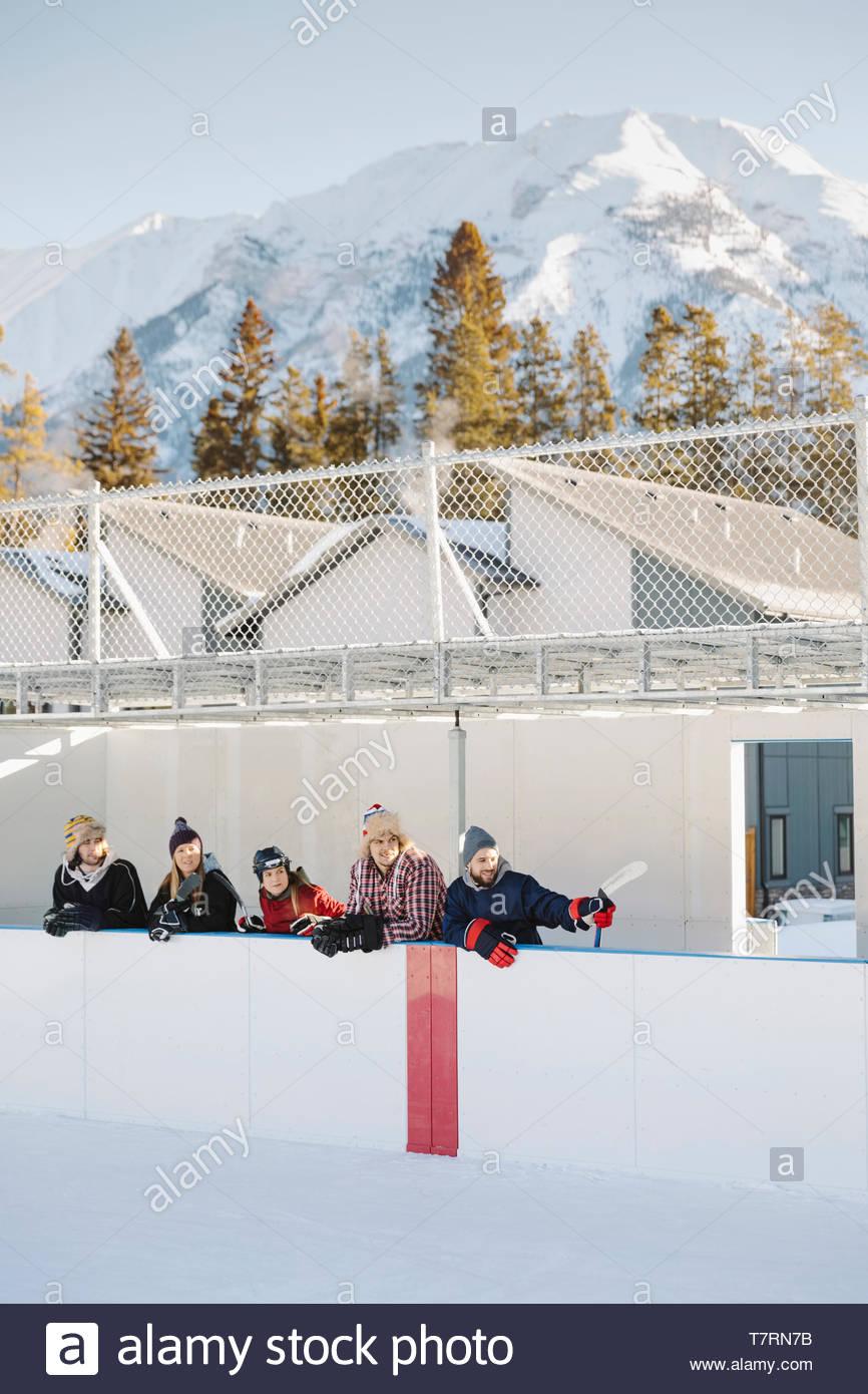 Amis sur la touche regarder le hockey sur glace en plein air au-dessous de la montagne enneigée Photo Stock