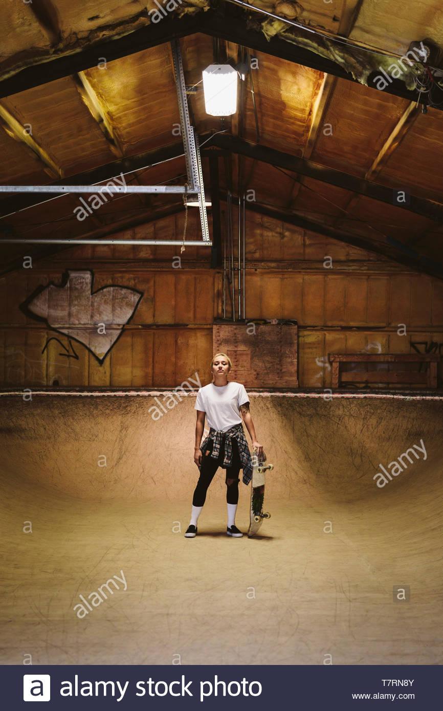 Confiant, Portrait jeune femme cool skateboarder à piscine skate park Photo Stock